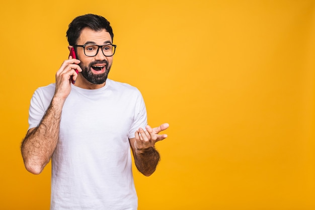 Oh, great news! smiling young casual bearded man talking on the phone isolated over yellow background.