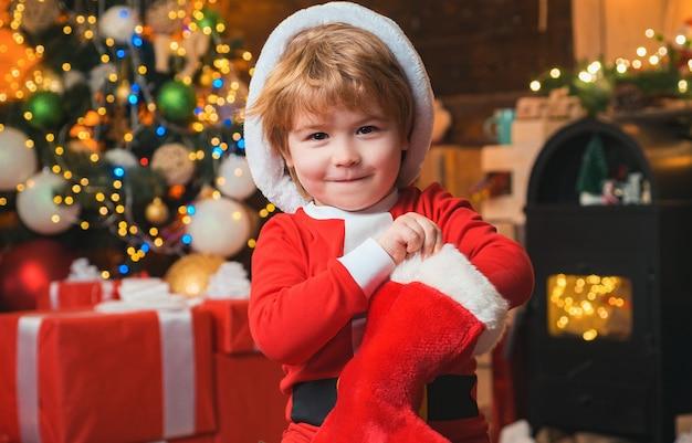 ああ幸せな日。子供の陽気な顔はクリスマスの靴下で贈り物をもらいました。