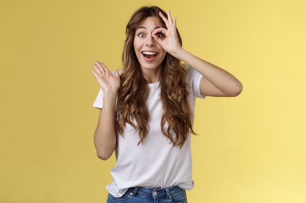 Oh ciao ti vedo. affascinante ragazza affascinante e carina che agita la palma saluta impressionato guarda attraverso il gesto dell'anello ok impressionato finalmente fisso vista stare stupito stupito sfondo giallo