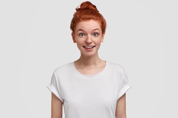 오, 그렇게 될 수 없습니다! 머리 롤빵을 가진 귀여운 여우 같은 빨간 머리 어린 소녀, 좋은 소식을 듣고 예기치 않은 시선으로 보이며 캐주얼 흰색 티셔츠를 입고 실내 모델