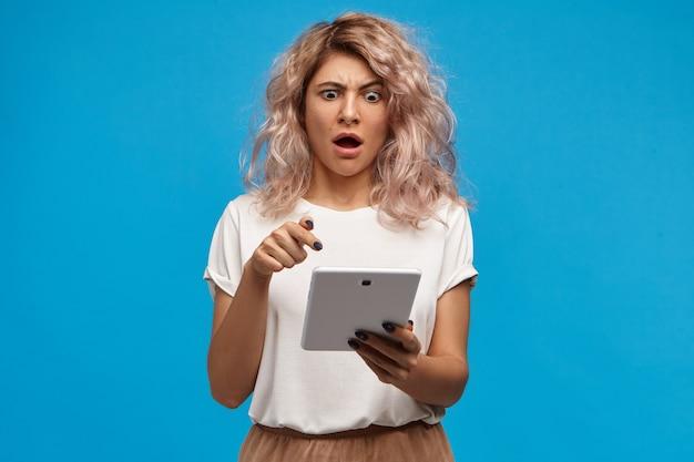 何てことだ。タッチパッドコンピュータを保持し、口を大きく開いて画面を指しているスタイリッシュな服を着た驚いたバグの目の学生の女の子