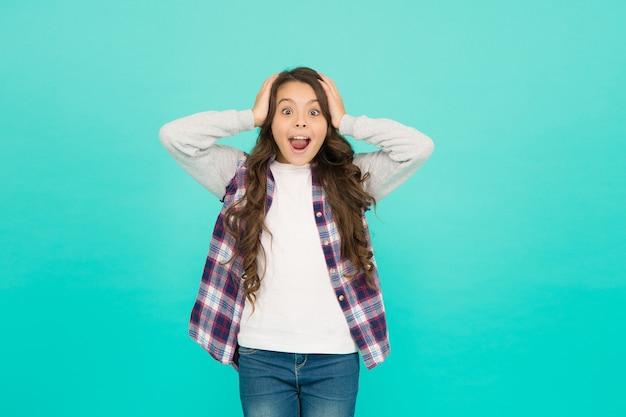 세상에. 아이는 트렌디한 캐주얼 재킷을 입는다. 아이 봄과 가을 패션. 작은 아름다움. 긍정적인 감정 표현하기. 행복 한 작은 소녀 청록색 배경입니다. 놀란 여학생은 긴 곱슬머리를 가지고 있습니다.
