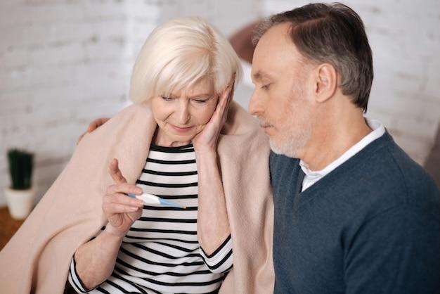 Боже ты мой. закройте вверх грустной старшей женщины, смотрящей на термометр, сидя покрытой одеялом рядом с ее мужем.