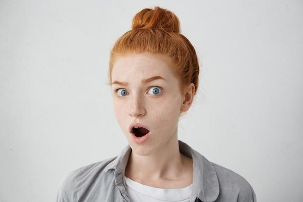 何てことだ!生意気な髪とそばかすが口を大きく開き、驚いたことに目を飛び出して、予期しないニュースやゴシップにショックを受けた面白いびっくりした若いヨーロッパ女性。