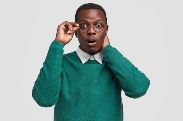 Oh my god, its disaster! stupefied dark skinned man realizes something went wrong, wears elegant sweater with shirt, notices something inappropriate