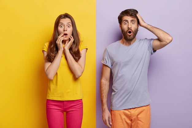 Oh my god! portrait of shocked stunned female and male popping eyes at camera, learn terrible news, pose in stupor