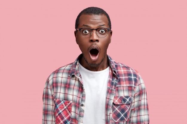 세상에. 놀란 짙은 피부의 아프리카 계 미국인 남성이 충격을받은 표정으로 카메라를 응시하고 안경과 체크 무늬 셔츠를 입습니다.