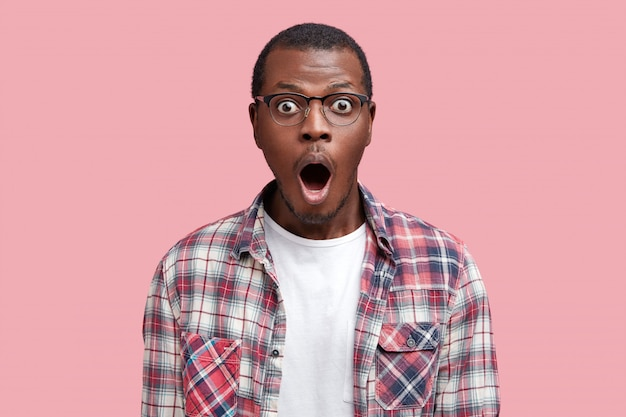 Oh my god. surprised dark skinned african american male stares at camera with shocked expression, wears spectacles and checkered shirt
