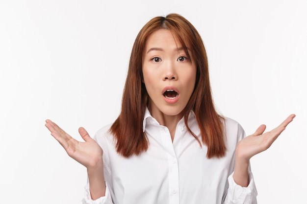 Oh my god what happened. close-up portrait of concerned and shocked young woman raising hands sideways and gasping startled, hear bad news, showing empathy, stand white wall