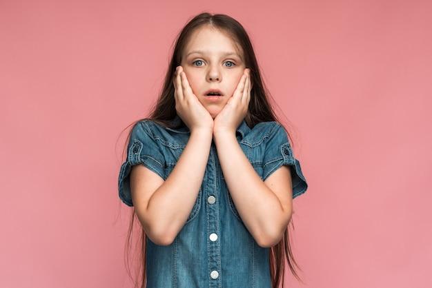 なんてこった、すごい!驚いた表情でカメラを見て、驚いて顔を合わせているおかしな驚愕の就学前の女の子の肖像画。ピンクの背景に分離されたスタジオショット