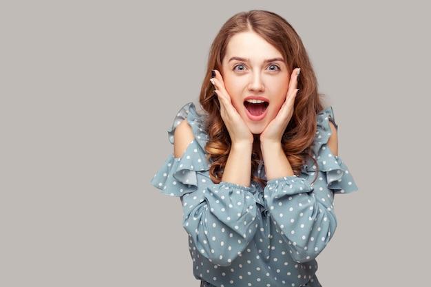 なんてこった、すごい!カメラを見て顔に触れて驚いた興奮したブルネットの女の子フリルブラウス