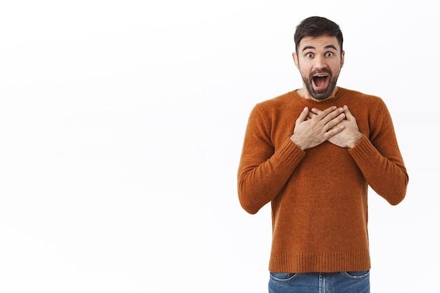 О, черт возьми, какой сюрприз. портрет изумленного и изумленного счастливого бородатого мужчины держится за руки на сердце, задыхаясь от волнения и изумления, слышит отличные новости, белая стена