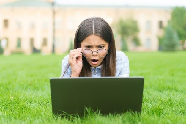 大野。学校に戻る。十代の少女は公園の緑の芝生でコンピューターを使用します。ノートブックとメガネの子。現代生活における新技術。勉強。ラップトップに取り組んでいる子供を驚かせた。オンライン教育。