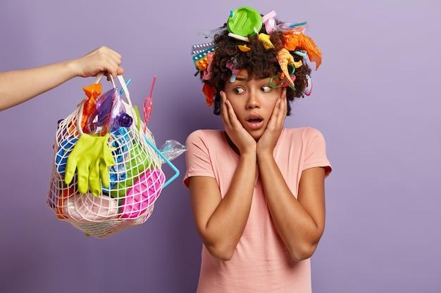오, 플라스틱 쓰레기로 자연을 오염시키지 마십시오! 불행한 민족 여자는 플라스틱 쓰레기로 가득 찬 가방에 충격을받은 표정으로 보이고, 행성을 청소하고, 실내 포즈를 취합니다. 지구의 날 및 자원 봉사 개념
