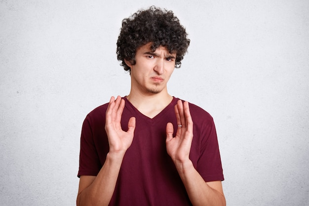 Oh no, don`t bother me! annoyed grumpy male with crisp hair, shows refusal gesture, poses against white background