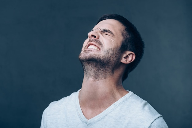 О, нет! разочарованный молодой человек держит глаза закрытыми и выражает негатив, стоя на сером фоне