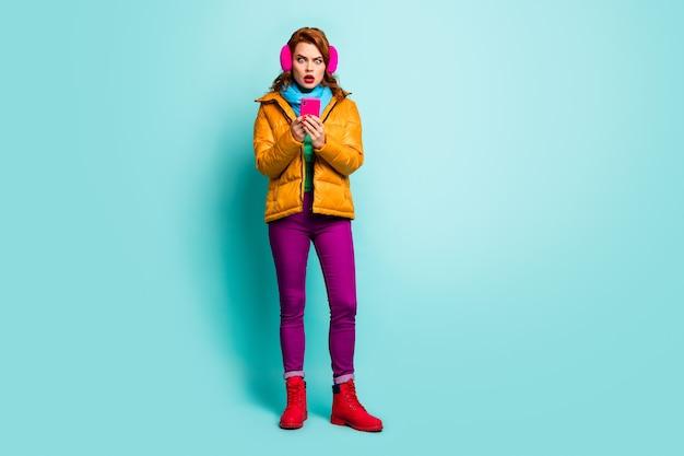 大野!旅行者の女性のフルサイズの肖像画は、電話を開いて口を開いて悪いニュースを読む流行のカジュアルな黄色のオーバーコートスカーフ紫のズボンの靴を保持します。