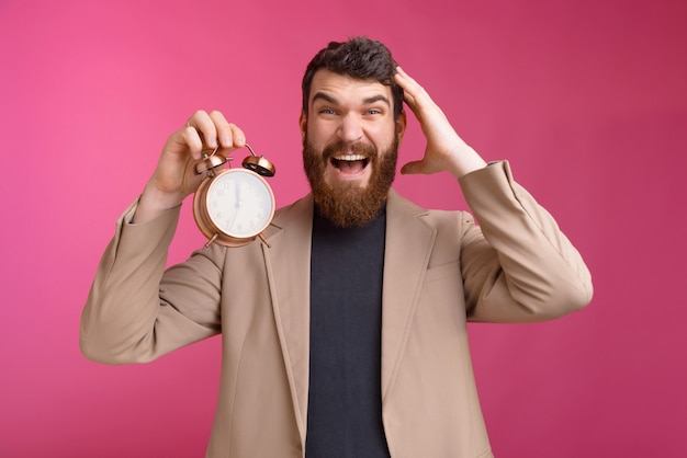 Oh no i am late. screaming bearded man is holding an alarm clock on pink wall.