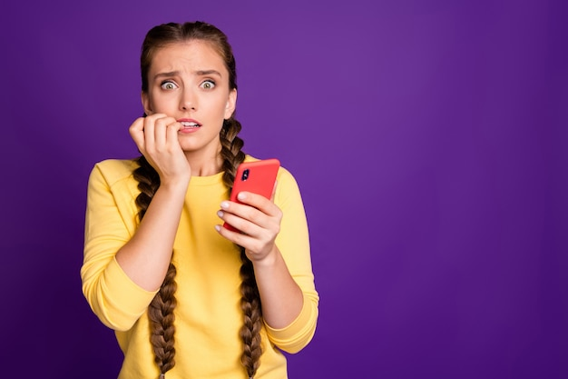 Oh no!  millennial lady holding telephone, eyes full of fear biting fingers wear casual yellow pullover isolated purple color wall
