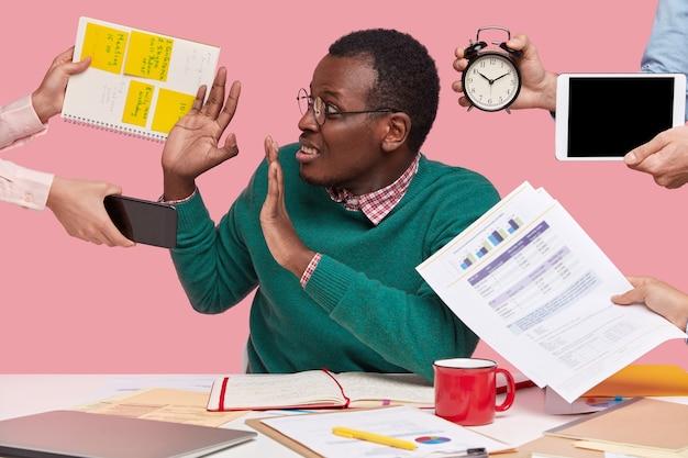 오, 지금은 안돼! 스트레스를받은 어두운 피부의 남자는 사무실에서 많은 일을하고 있으며 비즈니스 프로젝트 준비를 상기시키는 많은 사람들이 한 번에 요청하고 알람 시계를 들고