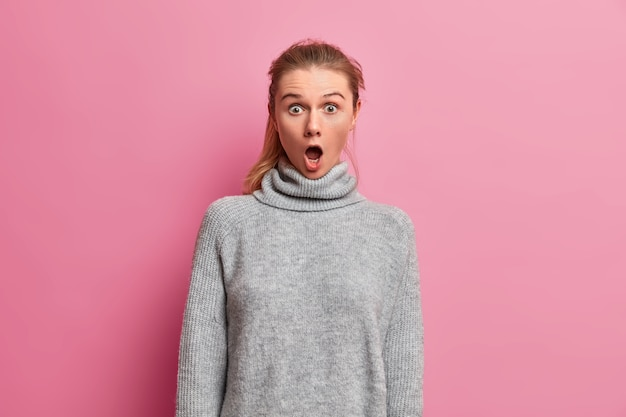 Oh no! shocked young woman keeps jaw dropped, reacts to something breathtaking, stares speechless, wears warm grey sweater