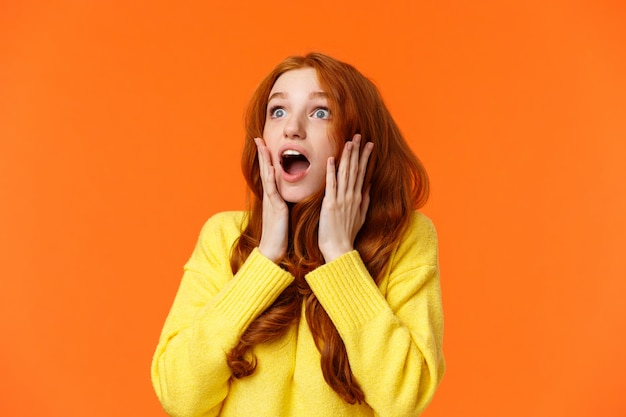 Oh no something falling from sky. shocked and speechless, startled young concerned redhead woman