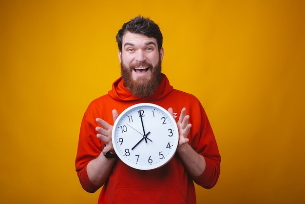 Oh no, what time is it. bearded  surprised man is holding a white clock on yellow space.