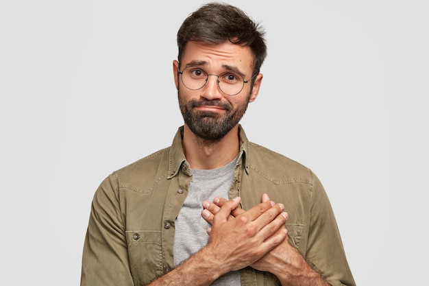 Oh, thank you very much! attractive unshaven young male keeps hands on heart, expresses gratitude, stands against white wall. friendly bearded caucasian guy being thankful to best friend