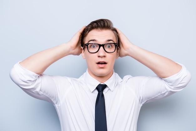ああすごい!本当に?!若いハンサムな学生は、純粋な空間に立って、フォーマルな服装と黒のスタイリッシュなメガネで頭を抱えてショックを受けています