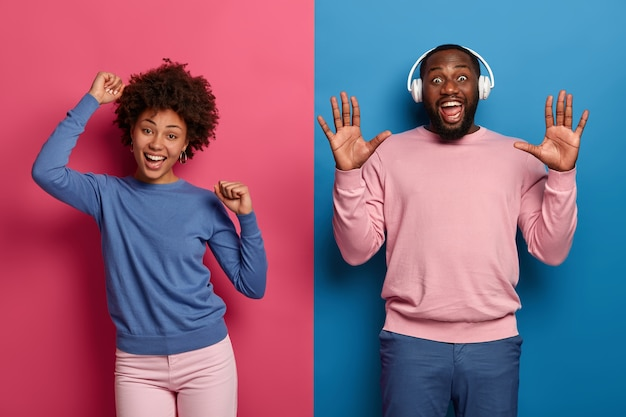 Oh yes its our song! joyful millennial curly woman and man dance and have fun, unbothered about opinion, celebrate passed exam, make disco move