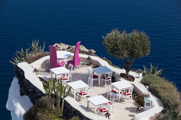 Ия, греция - 30 мая 2016: сцена побережья эгейского моря с рестораном, в ия, остров санторини, греция