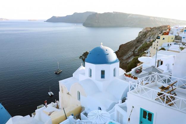 Город ия на острове санторини, греция. традиционные и известные дома и церкви с голубыми куполами над кальдерой, эгейское море, греция.