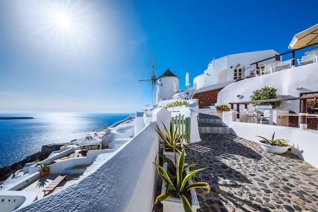 Oia village with sun, santorini island, greece