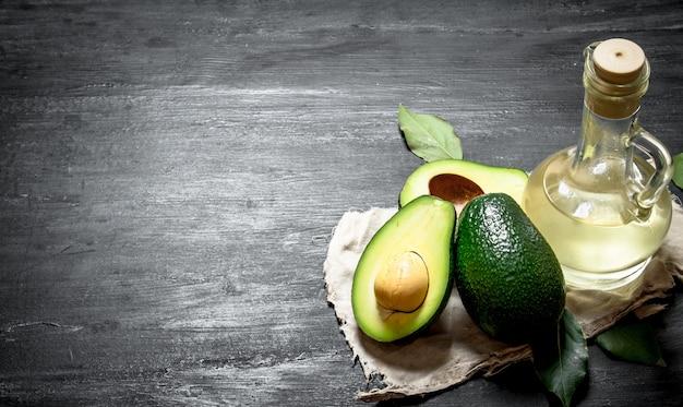 Масло и авокадо. на черном деревянном фоне.