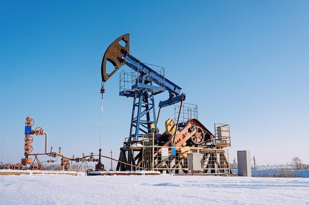 Нефтегазовая промышленность. рабочий домкрат масляного насоса на нефтяном месторождении в зимний солнечный день. добыча нефти в сибири.