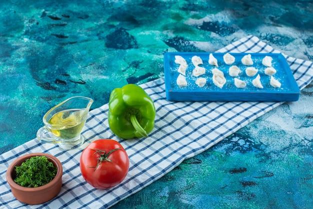 青いテーブルの上のティータオルのボード上のトルコのラビオリの横にある油と野菜。