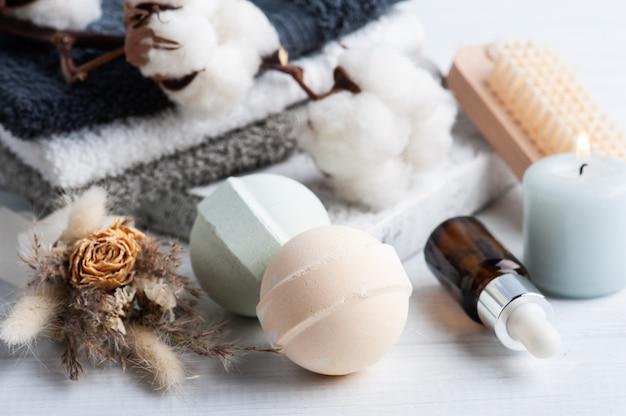 Бутылка масла и ароматические бомбы для ванн в спа-композиции с сухими цветами и композицией