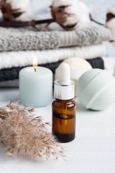 Бутылка с маслом и ароматические бомбы для ванн в спа-композиции с сухими цветами и полотенцами