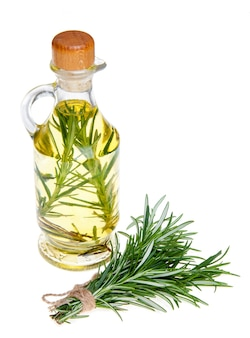 Oil in a bottle and fresh organic rosemary isolated on white