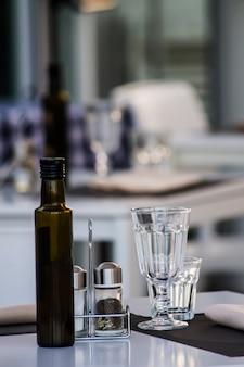 Oil bottle, spices bottles and glasses on restaurant table