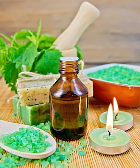Oil in a bottle, two bars of homemade soap, bath salt, two scented candles, nettles in a mortar on a wooden boards background