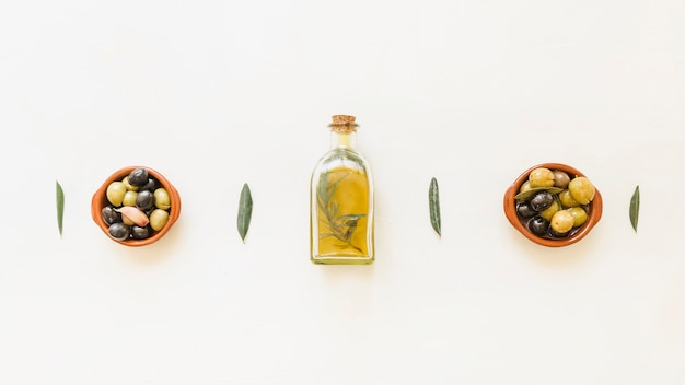 Oil bottle with bowls with olives