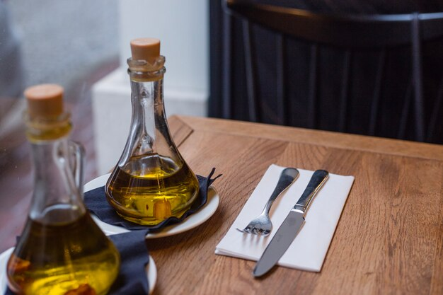 Oil bottles and cutlery on the wood table in a cafe
