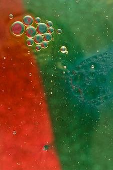 赤と緑の着色された水の塗料に浮かんでいる油泡