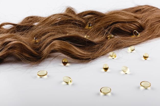 Масляные капсулы с витамином е лежат на коричневых волосах