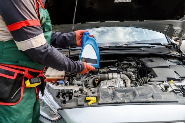Концепция замены масла. мужская рука в перчатке с бутылкой масла и автомобильным двигателем крупным планом