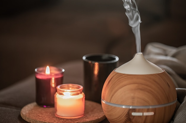 Oil diffuser near burning candles. aromatherapy and health care concept.
