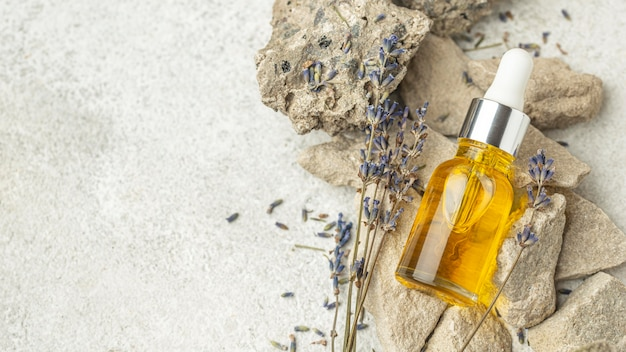 Contagocce dell'olio e lavanda sulle rocce con lo spazio della copia