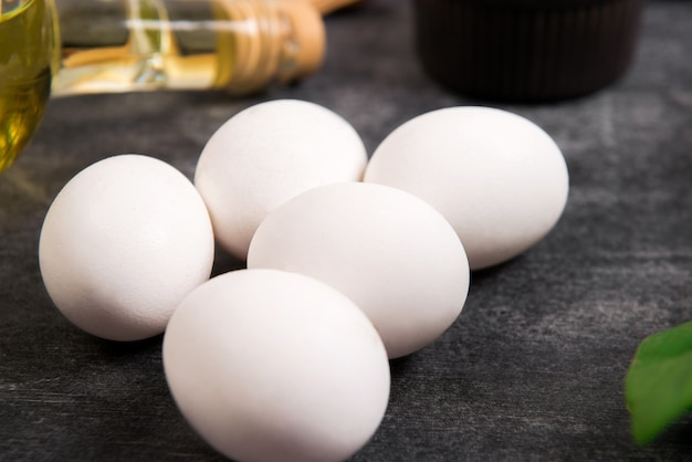Oil and eggs over grey wooden surface