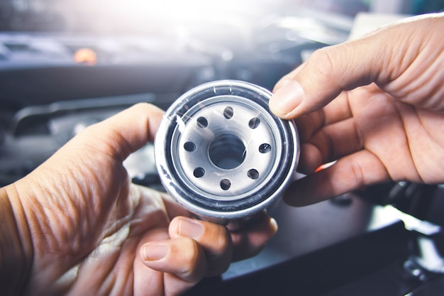 Масляный фильтр в руке механика для обслуживания масляной системы двигателя в ремонтной мастерской